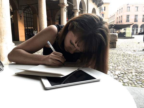 A woman sits in a plaza, leaning over a journal and ipad as she writes.