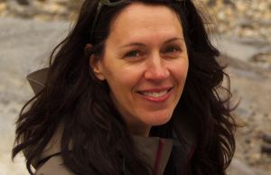 Photo of Chantal Bilodeau, a woman with long dark hair. She's wearing sunglasses on the top of her head. The background is a rocky river bank.