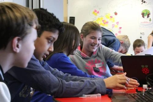 Several children, some smiling broadly and some concentrating intently, work with Raspberry PI computers and electronic components in a classroom