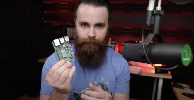 Network Chuck holding a Raspberry Pi 4 next to his broadcasting microphone