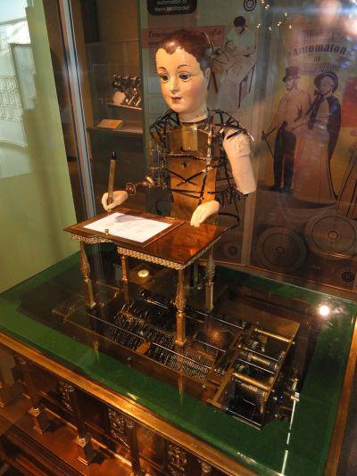 Mekaniske dukker var populære på sytten- og attenhundretallet. Dette er en maskin laget av Henri Maillardet cirka 1800, som kan tegne og skrive. Bilde: Daderot.