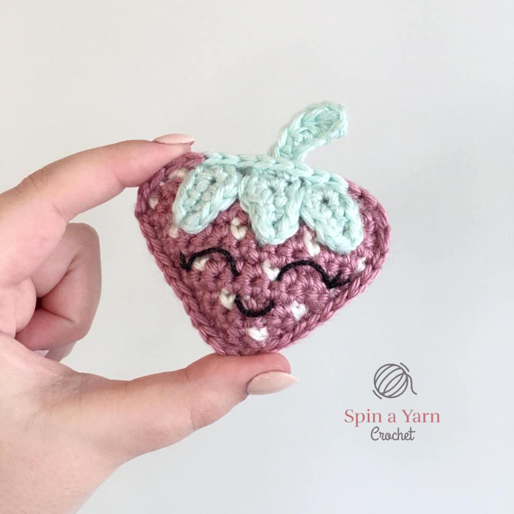 Crochet strawberry between fingers