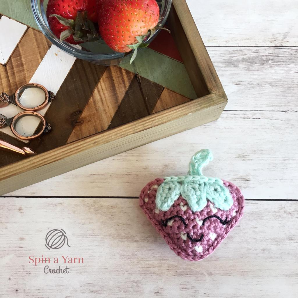Crochet strawberry next to tray with bowl of strawberries