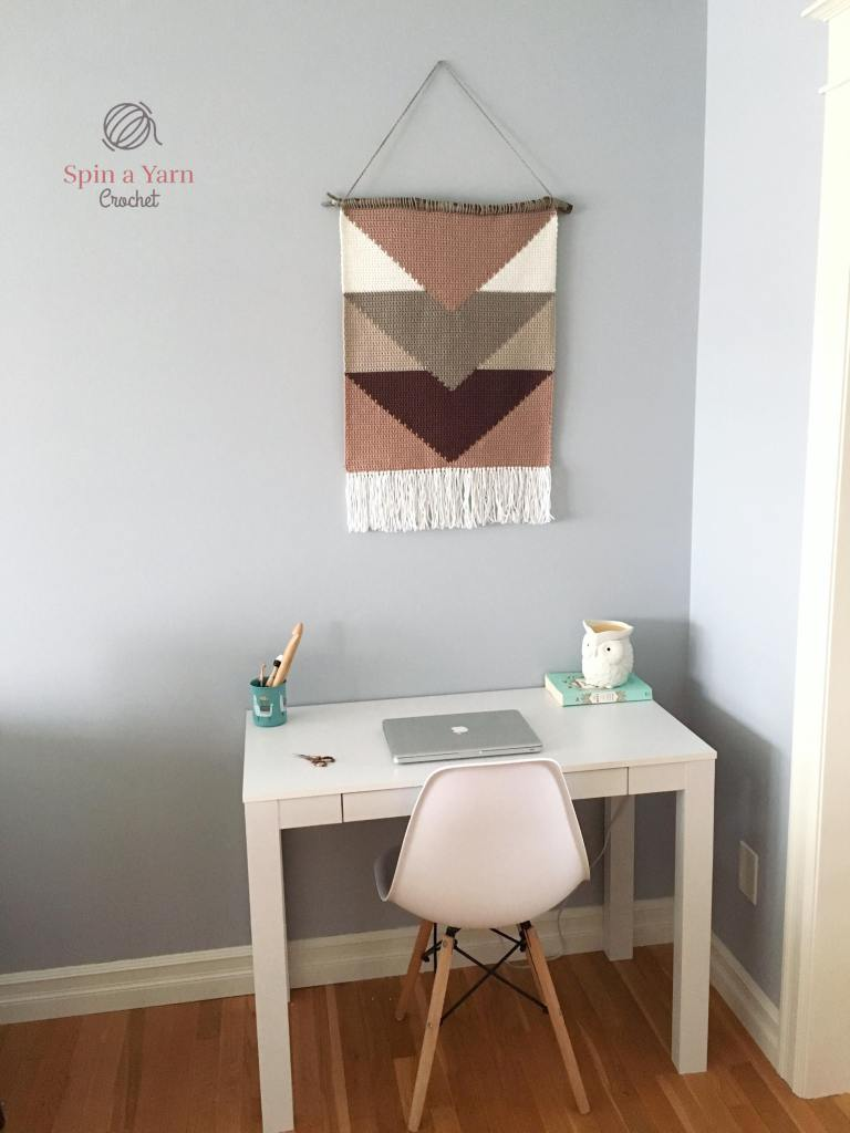 Wall hanging over desk with chair