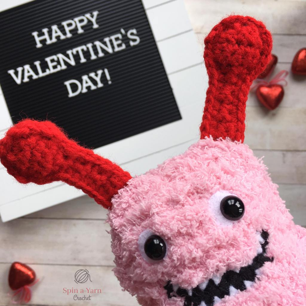 Love Monster in front of Happy Valentine's Day sign