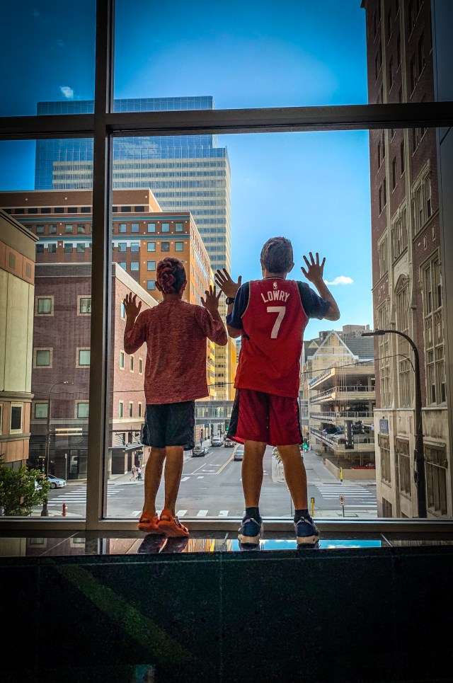Photo of two children standing on a ledge of the Minneapolis Skyway. They are leaning on a thick glass window looking down on the street below. Photo Credit:Spintheglobe.net