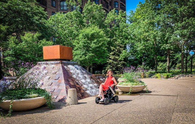 Photo features the writer of this blog in her wheelchair parked in-front of a fully accessible walkway next to a pyramid sculpture that features fountains of water flowing down from the top. Photo Credit:Spintheglobe.net