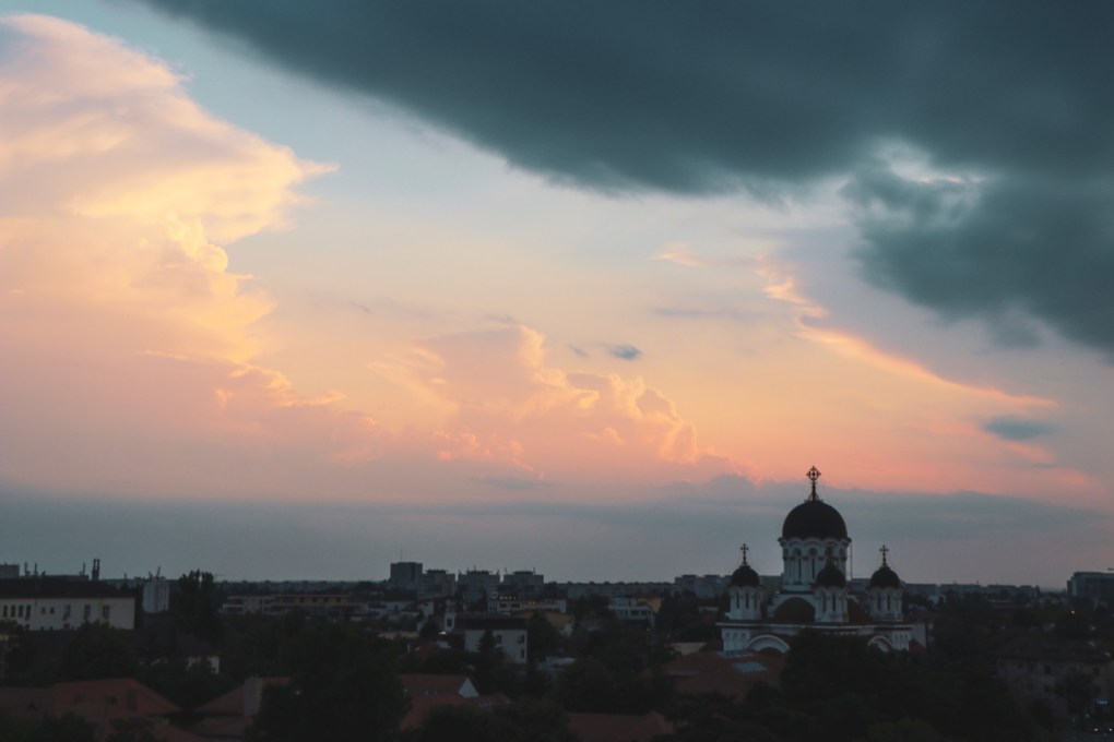 The sun sets over the skyline of Bucharest with a church in prominent view. 11 must-visit photo spots in Bucharest - spinthewindrose.com