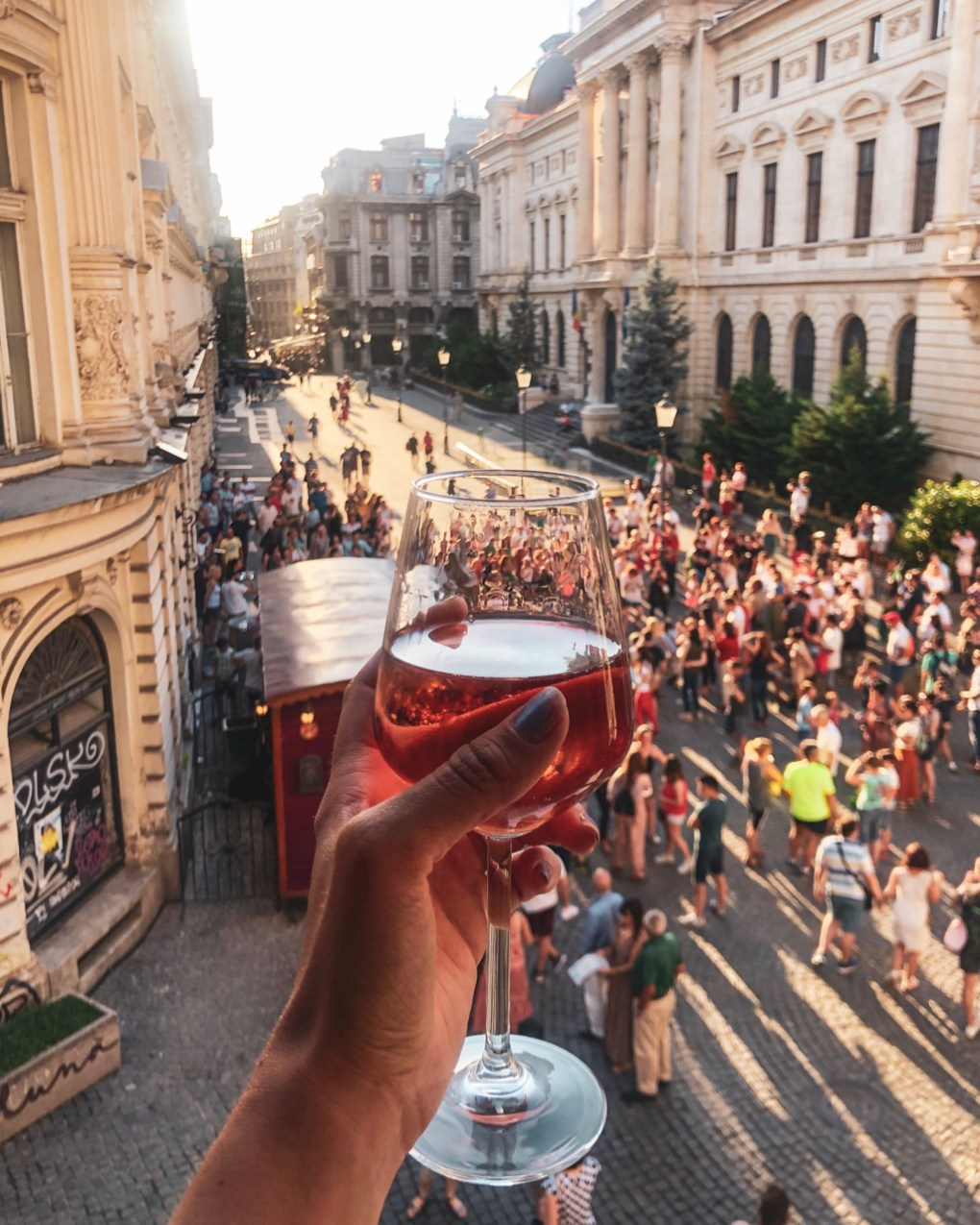 Raising a glass of wine at the view out of the window of Little Bucharest hostel, where a crowd gathers in the street below. 11 must-visit photo spots in Bucharest - spinthewindrose.com
