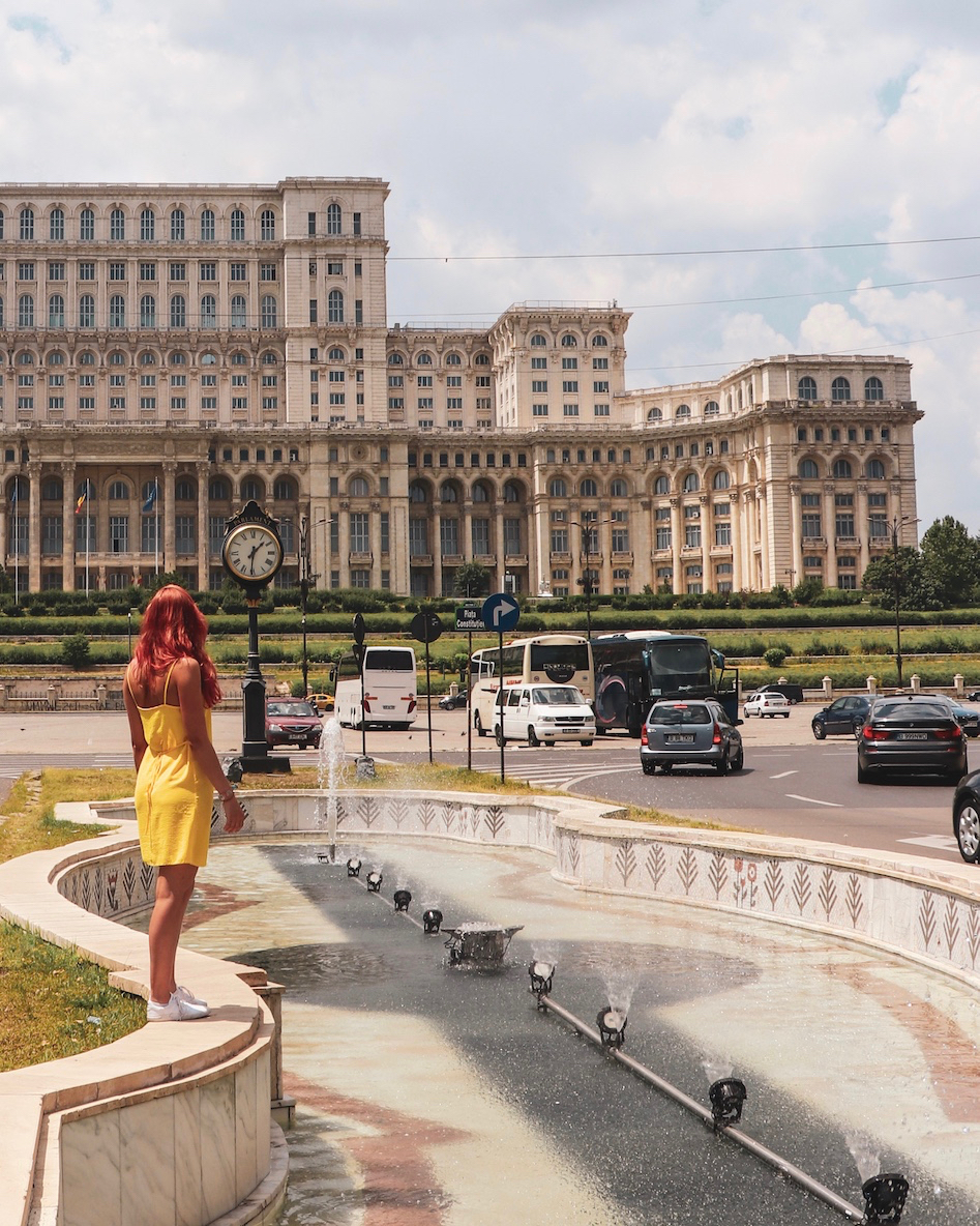 I'm standing wearing a yellow dress and looking away from the camera at the huge building. 11 must-visit photo spots in Bucharest - spinthewindrose.com