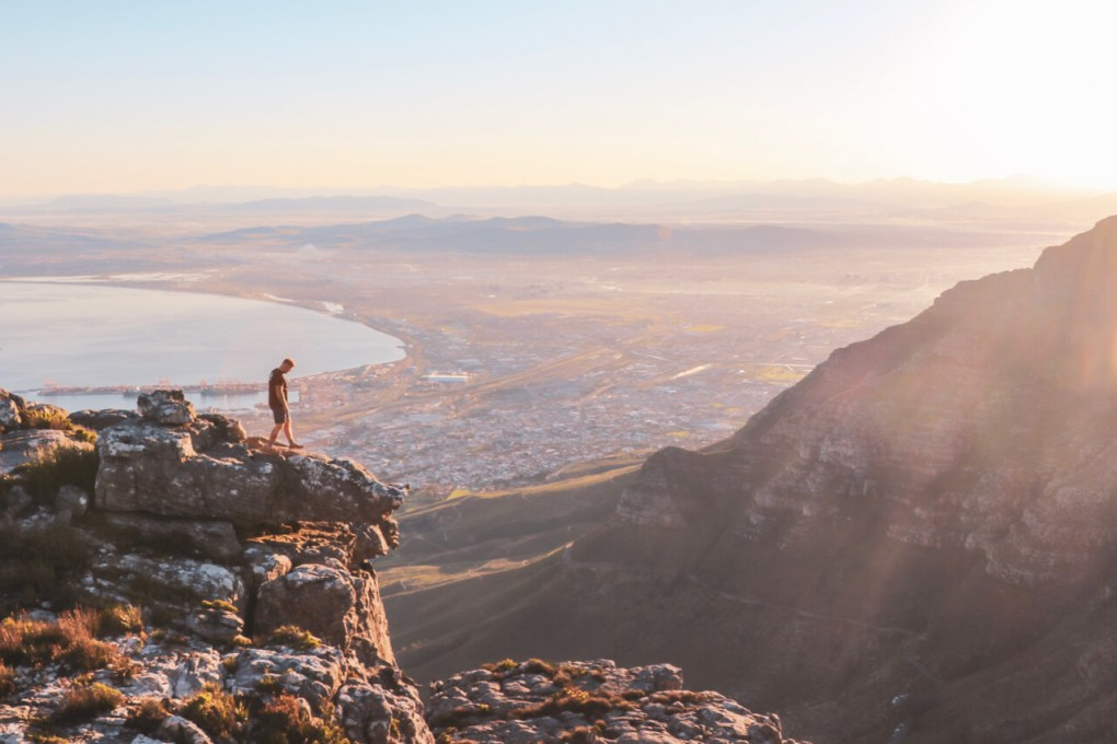A man stands on the edge of Table mountain clifface, overlooking the vast landscape of Cape Town below. The sun is rising, casting a beautiful glow across the scene.