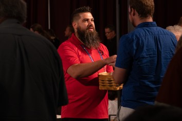 Josh Trader serving communion bread at the General Convention Closing Eucharist. Image: Gary Allman