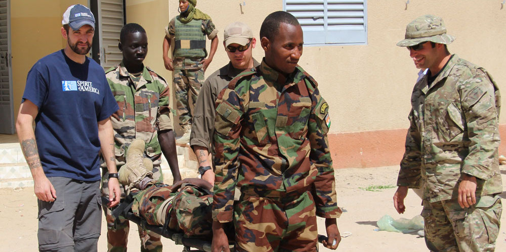 SoA's Isaac Eagan delivers a stretcher to soldiers in Niger to help them stop Boko Haram