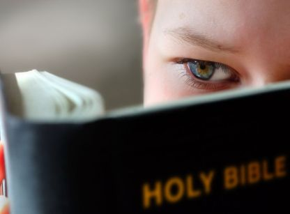 A child reading the story of God in the Bible.