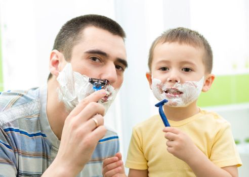 A son imitates his father shaving