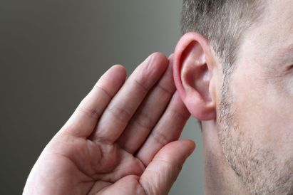 A man holding his hand to his ear, listening. In his parables, Jesus calls us to listen to difficult teachings.