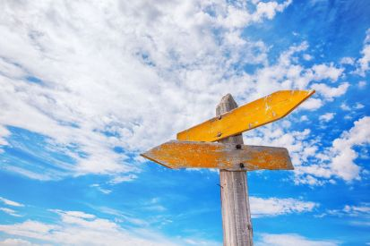 A yellow, rustic signpost against a cloudy sky. Which direction will you choose?