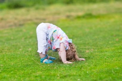 A toddler standing bent over with her head on the grass.