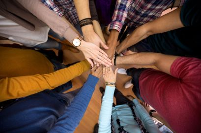 Many hands united in the middle. The Spirit unites us all.