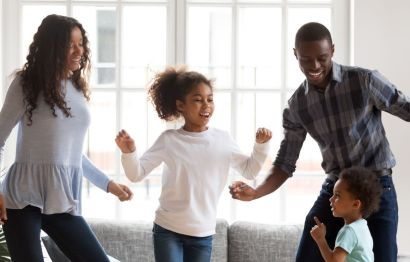 Happy family dancing at home.