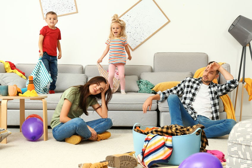 Stressed out parents and two children running wild in a messy living room.