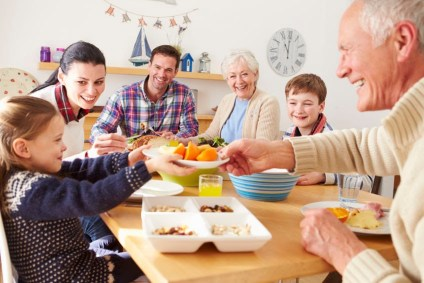 An intergenerational family sharing a meal together. Passover is also celebrated with an intergenerational meal.