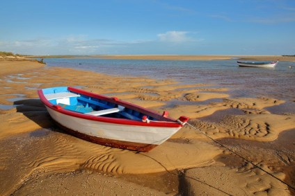 A rowboat left behind on a beach.