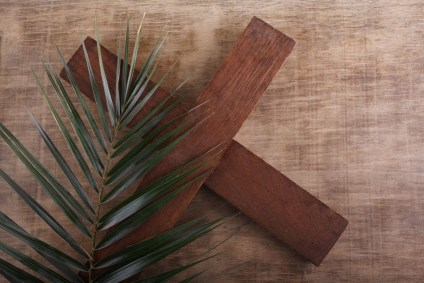 A wooden cross and palm frond on a brown background. Symbol of Holy Week.