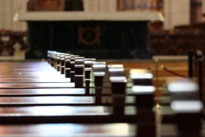 An image of empty church pews with an altar in the background.