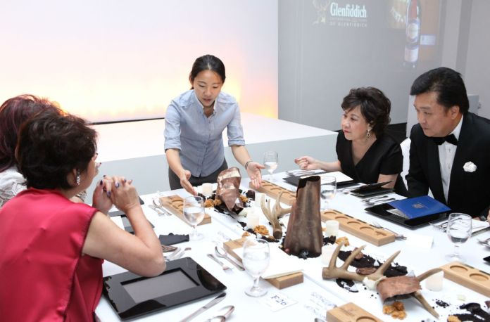 Chef Janice Wong explaining to guests the inspiration behind the edible art pieces