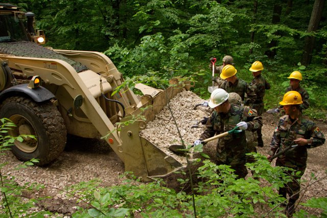 Moldovan and U.S. soldiers work together to build skills and forge stronger relationships while repairing a road