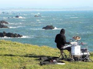 Batteur jouant de la batterie sur une falaise face à la mer