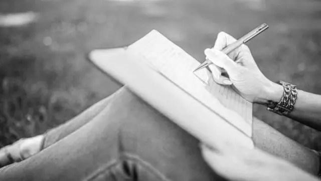 ノートに文字を書く女性 草むら 言葉