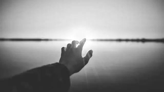 海に沈む夕日 手を伸ばす