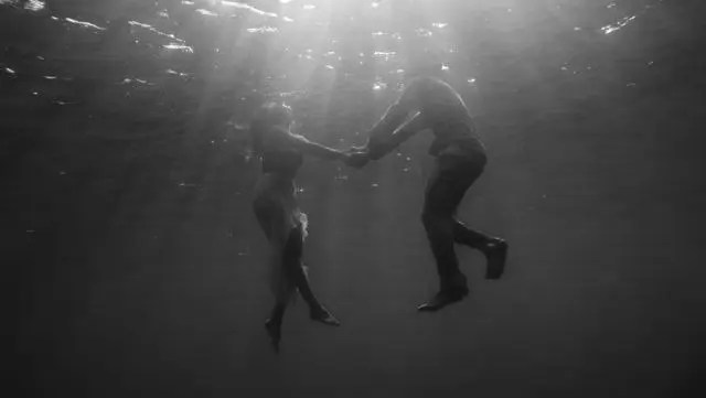 潜水するカップル 海 湖 手をつなぐ