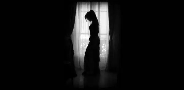 暗い部屋でうなだれる女性 失恋