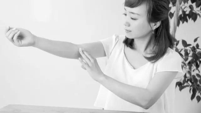 腕にクリームを塗る女性 肌 皮膚