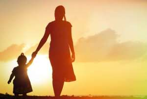 mother and little daughter walking on beach at sunset