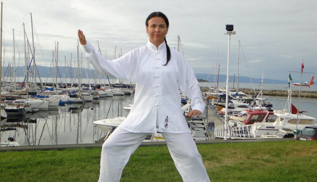 Svanhild i hvit Tai Chi drakt ute ved båthavn