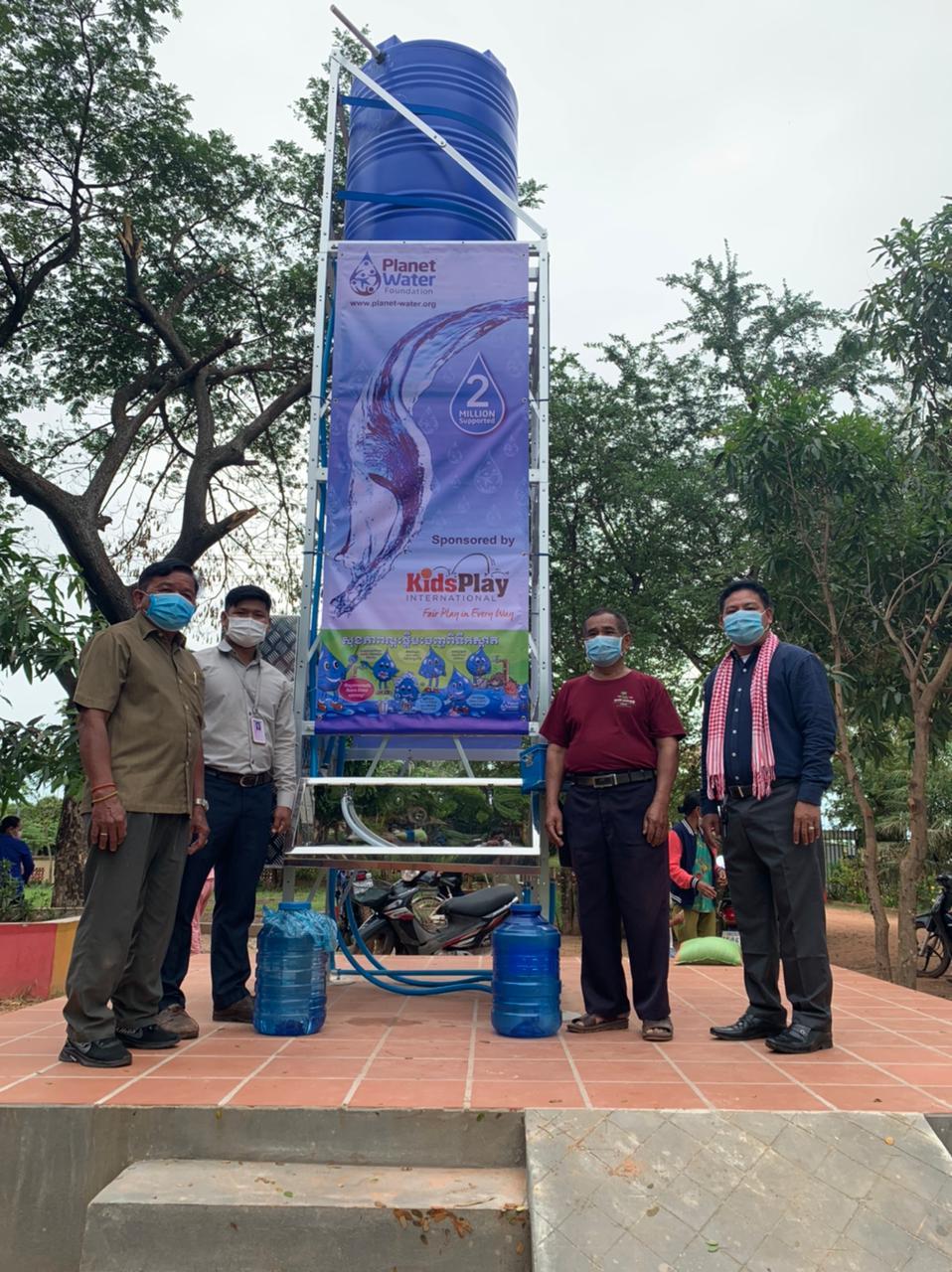 Staff at Kurata stand at new water tank