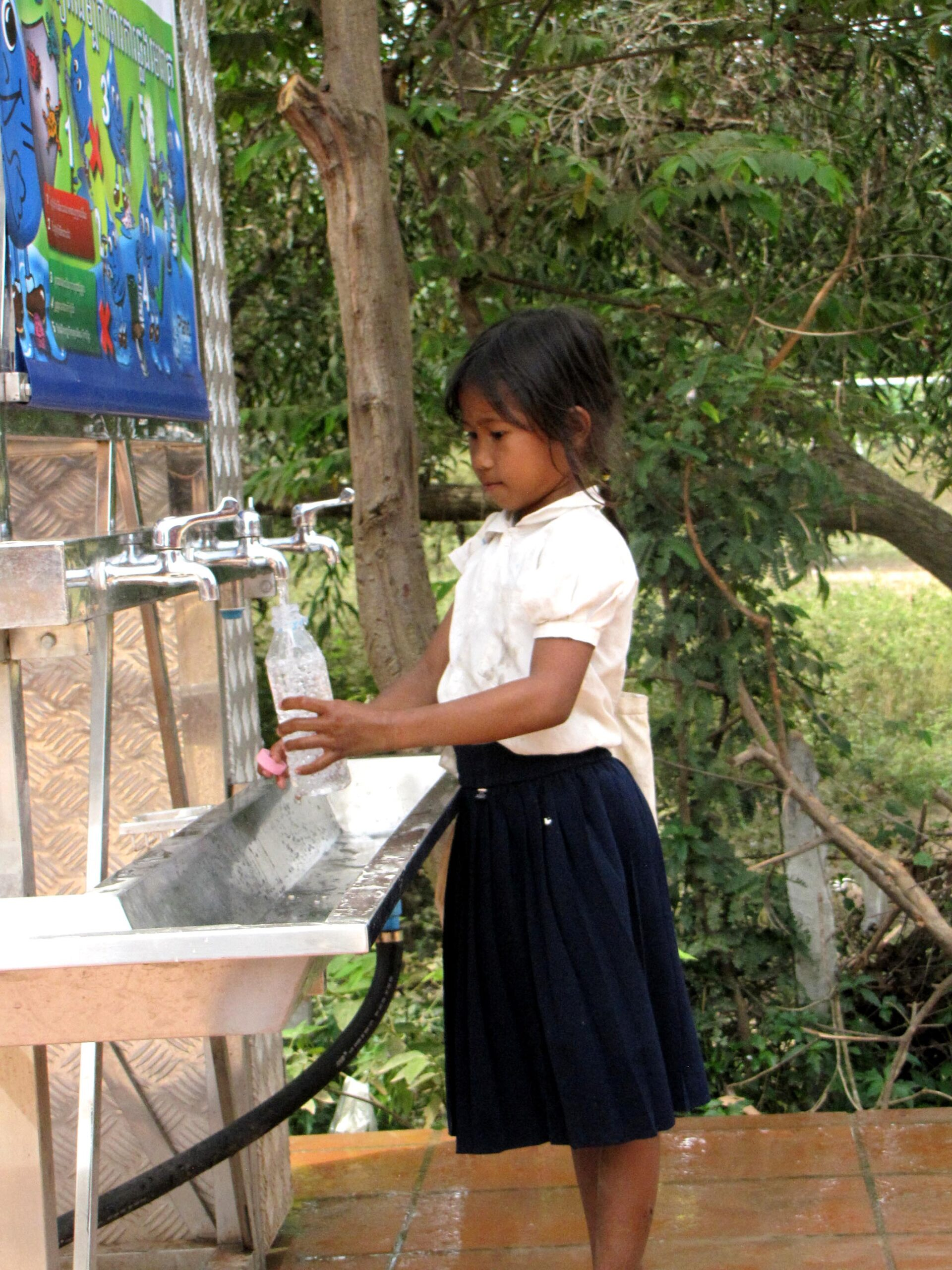 Young girl student gets water from Kurata tank