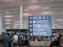 """The check-in lines at Air China in Beijing were a mess, but I smiled when I noticed that someone had added a letter s to the end of """"Restaurant"""" on this sign."""