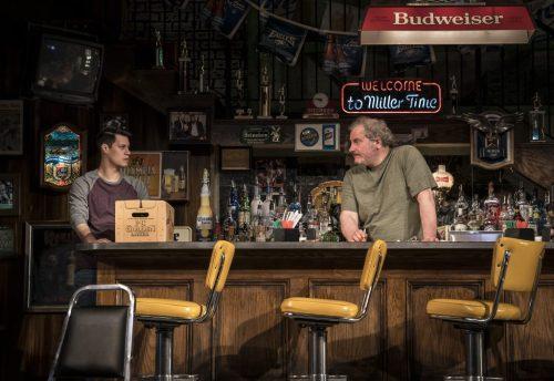 Two men behind a bar