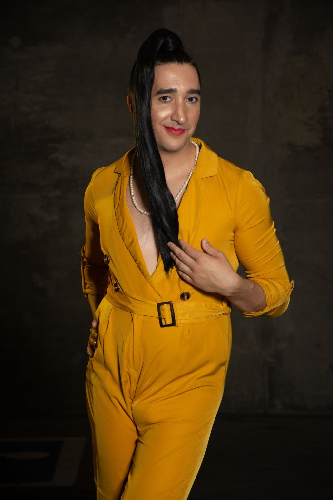 Person with a long dark ponytail and yellow jumpsuit