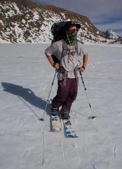 Skyler Gallardo skinning across a frozen lake with Mt Dana in the background