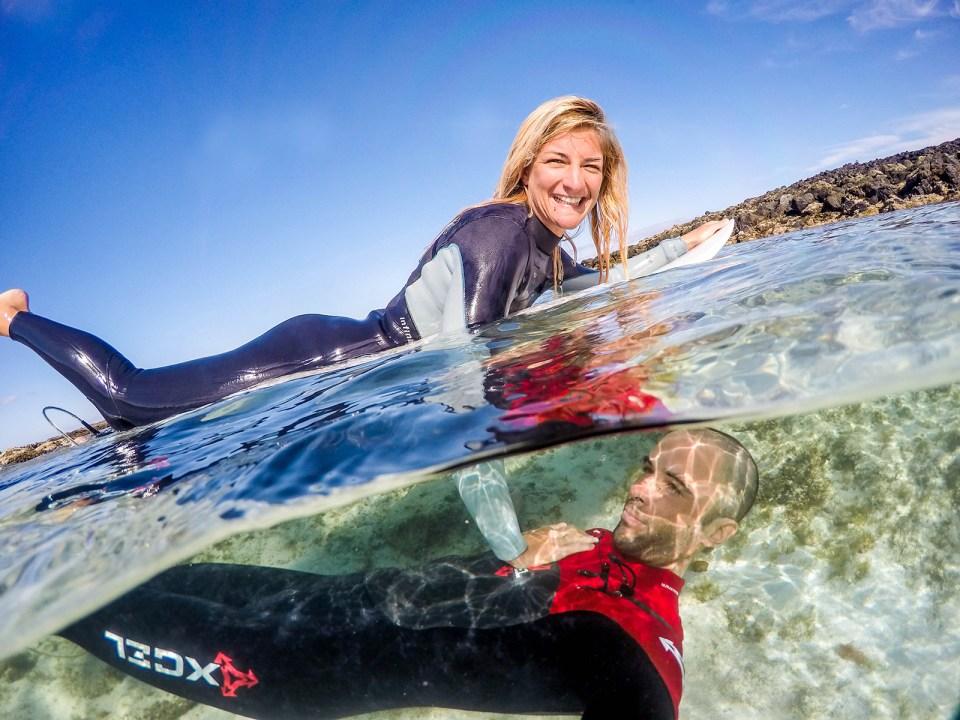 Surf couple having fun in the sea half half photo