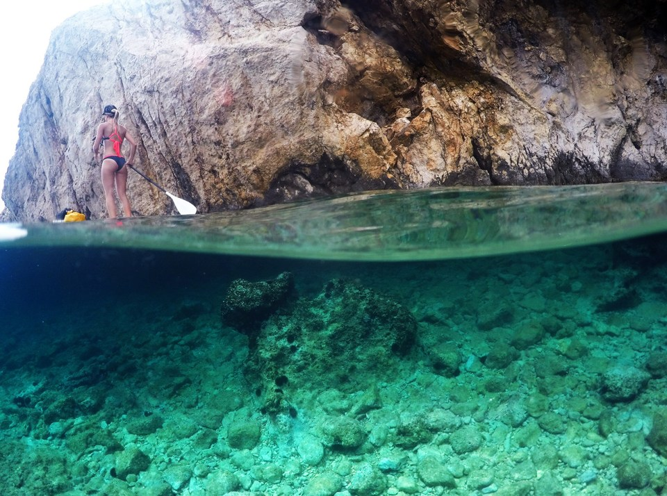 Bikini girl stand up paddling over rocky bottom sea amazing half half photo