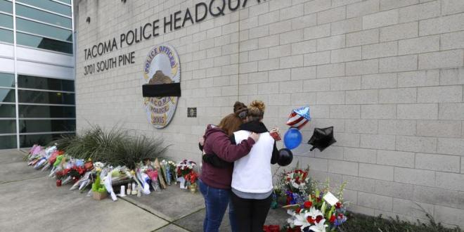 Three women embrace as they stand at a growing memorial Thursday at the Tacoma Police Department headquarters in Tacoma, Washington. A Tacoma Police officer died Wednesday night at a hospital after being shot multiple times earlier in the day while answering a domestic violence call. A Spokane woman thinks shooting a police officer should become a hate crime under Washington law. (Ted S. Warren / AP)