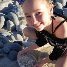 Kassie holding a rock with a fossil of a shell