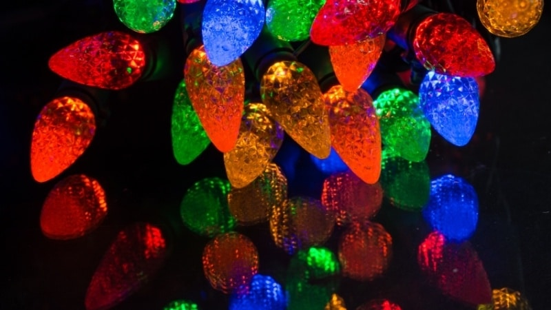 Large blue, red, green, and amber LED Christmas lights against a black background.